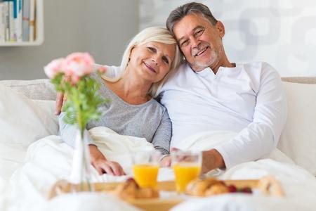 enjoying life: Senior couple enjoying breakfast in bed Stock Photo