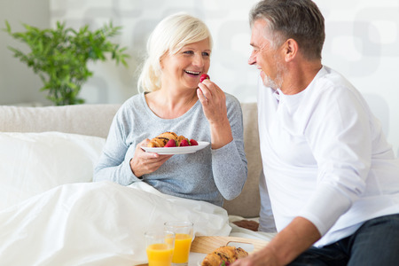 happy senior: Senior couple enjoying breakfast in bed Stock Photo