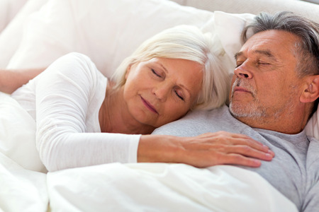 Senior couple lying in bed together Stock Photo