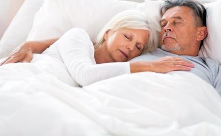 pareja durmiendo: Senior couple lying in bed together Foto de archivo