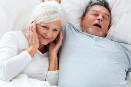 awake: Senior man snoring and woman covering ears Stock Photo