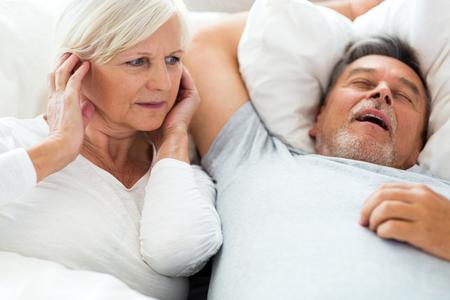 Senior man snoring and woman covering ears Standard-Bild
