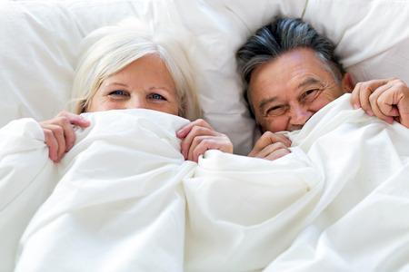 一緒にベッドで横になっている年配のカップル 写真素材