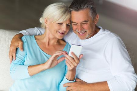 휴대 전화를 사용하는 노인 부부