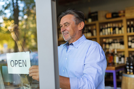 Wine shop owner holding open sign 写真素材