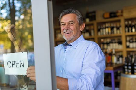 Wine shop owner holding open sign Archivio Fotografico