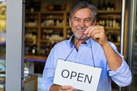 Wine shop owner holding open sign Standard-Bild