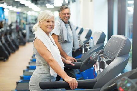 Senior couple exercising in gym Foto de archivo