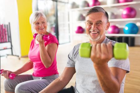 Senior couple exercising in gym 写真素材