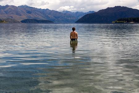 Man standing in still remote lake photo