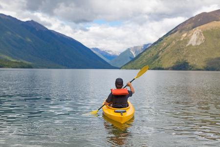 Man paddling a kayak in mountain lake, Lake Rotoiti, New Zealand photo