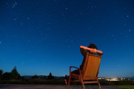 Man sitting in armchair under the stars photo
