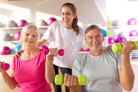 working out: Senior couple training in the gym with a personal trainer Stock Photo