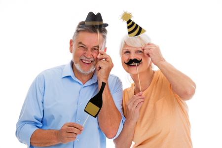 Funny senior couple holding party hats and mustaches on sticks