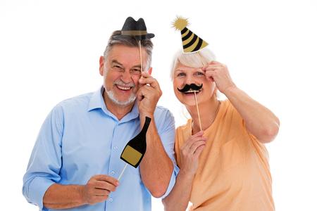 Grappige senior paar bedrijf partij hoeden en snorren op stokken Stockfoto - 76887392