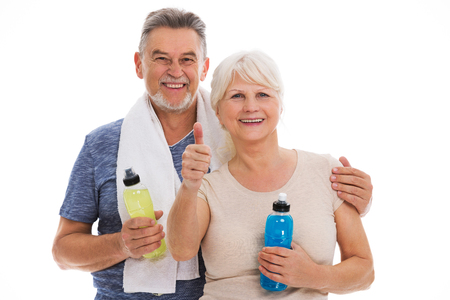 isotonic: Fitness senior couple with towel and bottles