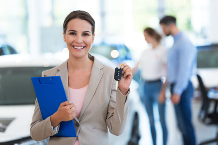 drivers license: Female car dealer standing in showroom