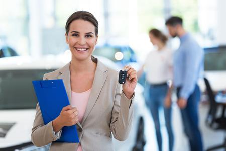 Vrouwelijke autodealer in de showroom
