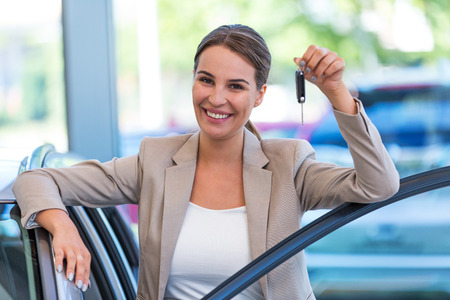 well dressed: Happy young woman with her new car