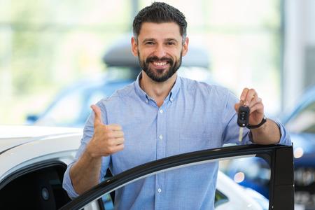 彼の新しい車と幸せな若い男