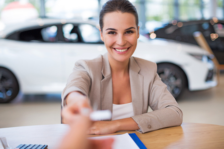 Female car dealer in showroom