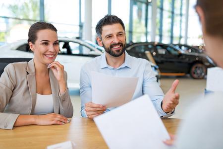 Jong koppel met auto dealers in de auto salon