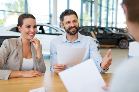 Young couple with car dealers in auto salon Stock Photo