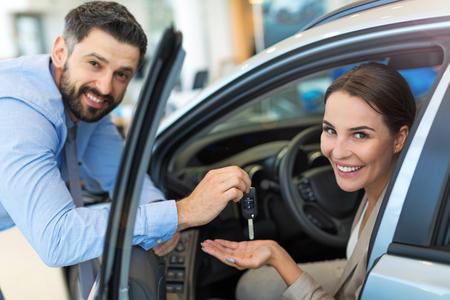 Woman receiving keys from a car dealer Imagens