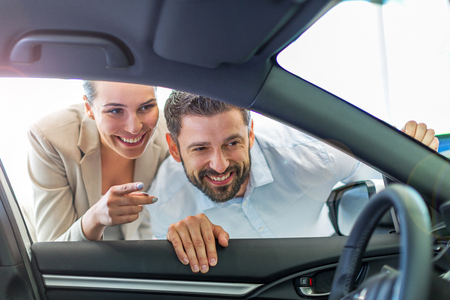 Young couple in the showroom, choosing a car Stock Photo