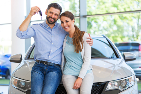 Young couple in the showroom, choosing a car Stockfoto