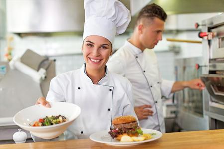 Two smiling chefs in kitchen Foto de archivo