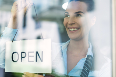 Woman holding open sign in cafe Standard-Bild