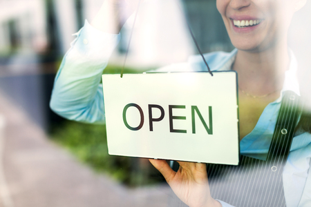 Woman holding open sign in cafe Banque d'images
