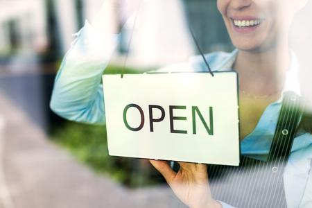 Woman holding open sign in cafe Foto de archivo