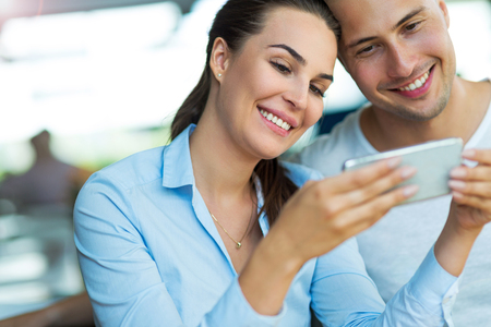 Young couple using mobile phone at cafe Stock Photo