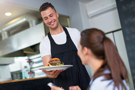 Waiter serving customer at restaurant photo