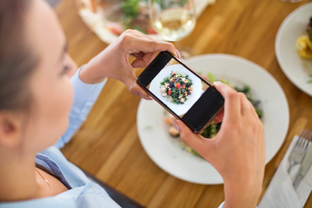 Woman with smartphone photographing food at cafe photo
