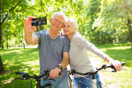 Senior couple with bicycles taking selfie