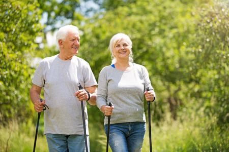 Senior couple Nordic walking in park
