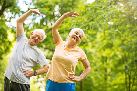 Senior Couple Exercising In Park Stockfoto