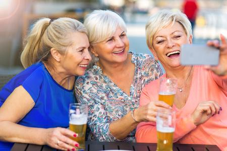 Mujeres mayores sonrientes que toman una cerveza en un pub al aire libre