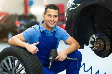 Car mechanic changing tires