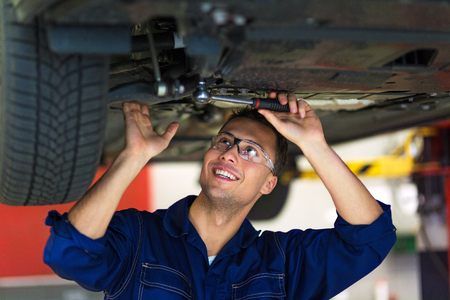 Car mechanic working on the underside of a car
