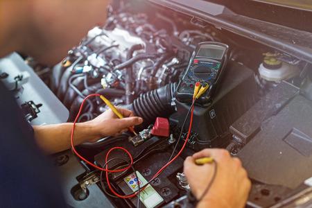 Mechanik samochodowy sprawdzający napięcie akumulatora samochodowego
