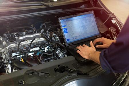Mechanic Using Laptop While die Motor van een auto onderzoeken