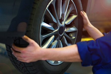 Car mechanic in workshop changing tires