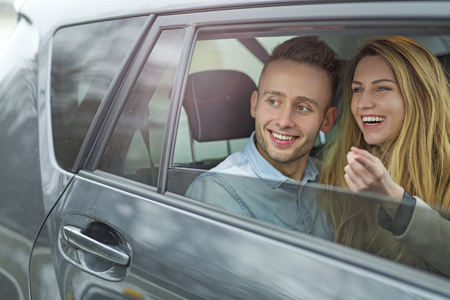Happy couple sitting in a car