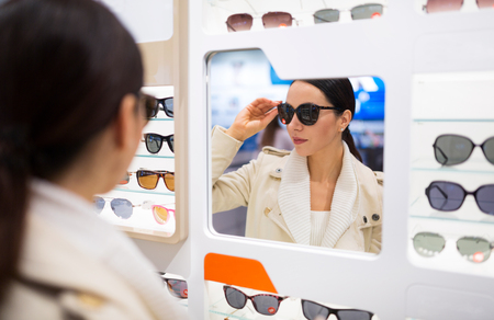 Woman choosing glasses in optician store Stock Photo