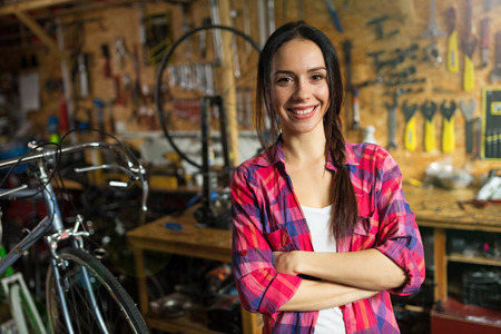 Confident young woman working in a bicycle repair shop Stock Photo