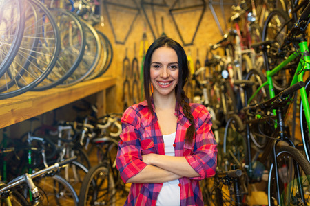 Young woman working in a bicycle repair shop